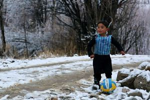Wearing his Lionel Messi plastic bag jersey, Afghan boy Murtaza Ahmadi plays football in the Jaghori district of Ghazni province.