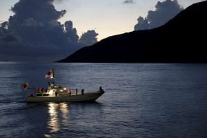 A fishing boat featuring Japanese flags sails around the disputed Senkaku Islands in the East China Sea.