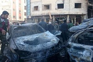 Residents and soldiers loyal to Syria's President Bashar al-Assad inspect damage after a suicide attack in Sayeda Zeinab district in Damascus, Syria, on Jan 31, 2016.