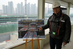 Hanwha Engineering and Construction's Park Hee An, who is overseeing the construction of the Dongtan high-speed rail station, with an artist's impression of the station. Behind him is the building site.