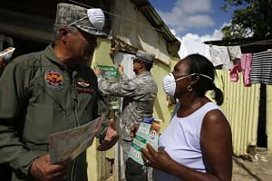 Members of the Dominican army giving residents of Guerra in the Dominican Republic information to help prevent the propagation of the Aedes aegypti mosquito, transmitter of the Zika virus. The WHO says as many as four million people in the Americas m