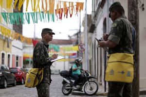 Brazilian soldiers conducting an inspection for the Aedes aegypti mosquito on a street in Recife, Brazil, on Feb 1, 2016.