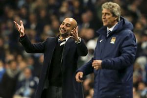 Pep Guardiola (left) reacts next to Manuel Pellegrini during a Champions League match in Manchester on Nov 25, 2014.