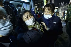 A woman is comforted as rescue personnel continue work at the site of a collapsed building following the earthquake.