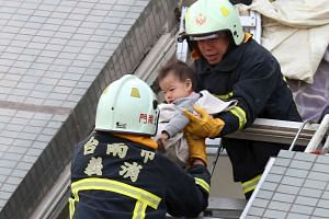 Rescue workers removing a baby from the site where a 17-storey apartment collapsed after an earthquake hit Tainan on Feb 6.