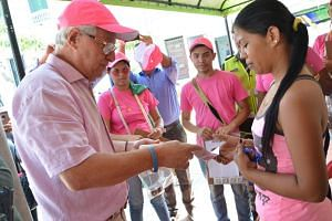 Soledad mayor Joao Herrera (left) giving out condoms and kits with insect repellent during a campaign to fight the spread of Zika virus in Colombia on Feb 1.