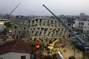 Rescuers search for survivors from a collapsed building following a 6.4 magnitude earthquake in Tainan City, Taiwan on Feb 7, 2016.