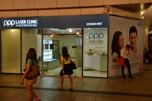 People walking past the Bishan branch of the PPP Laser Clinic.