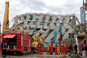 Rescuers standing beside a collapsed building in Tainan City, south Taiwan on Feb 10, 2016.