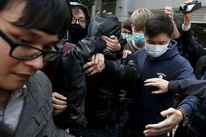 A suspect being covered by a jacket with supporters surrounding him as he leaves to go on bail at a court in Hong Kong, China, on Feb 11, 2016. Dozens of people in Hong Kong were charged on Thursday with taking part in a riot after a dispute between