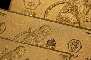 Gold bars featuring illustrations of monkeys sit on display in Hong Kong China.