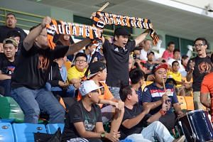 Showing spirit and commitment, Hougang United fans brandish scarves emblazoned with the acronym HOOL (Hougang Only One Love) at a friendly match against Tampines Rovers on Jan 9 at the Jalan Besar Stadium.