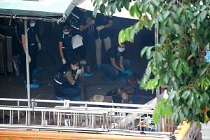 Police investigators examining the body of Mr Tan Poh Huat inside the Chua Chu Kang Lian Sing Keng temple.