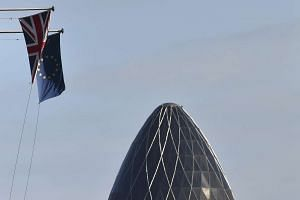 A British Union Jack flag and an European Union flag fly from a building, with the 'Gherkin' skyscraper seen in the City of London financial district in London, Britain, on Jan 30, 2016.
