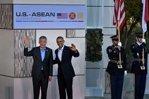 Prime Minister Lee Hsien Loong and US President Barack Obama waving to the media during the US-Asean leaders summit.