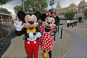 Actors clad as cartoon characters Mickey Mouse and Minnie Mouse at Hong Kong Disneyland Resort.