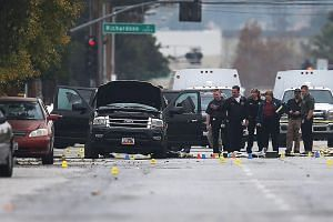 Law enforcement officials conducting their investigation around the vehicle used by Syed Farook and Tashfeen Malik (below) at the scene of the police shootout with the couple last December. The couple gunned down 14 people at an office party before t