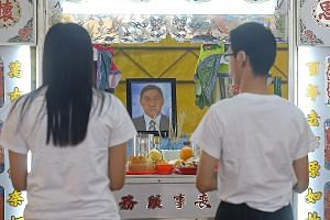 Mr Tan's daughter and 32-year-old son, Junqiang, at his wake yesterday at Teck Whye Avenue. Mr Tan especially doted on Junqiang, who lives in a centre for people with special needs on weekdays, said family and friends.