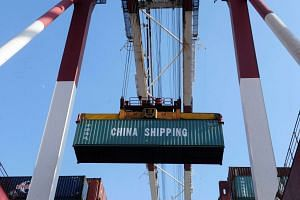 A container is lifted by a crane at the port in Qingdao, in China's Shandong province on Feb 15, 2016.