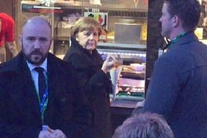 A hungry Angela Merkel pops out for chips.