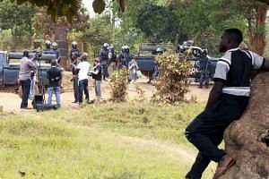Members of the media are seen as riot police block a driveway leading to the home of Kizza Besigye.