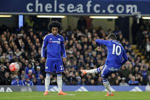 Chelsea's Eden Hazard scores their forth goal against Manchester City next to Willian (left) on Sunday (Feb 21).