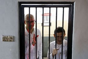 Canadian teacher Neil Bantleman (left) and Indonesian teaching assistant Ferdinand Tjiong in a holding cell before their trial in Indonesia, on April 2, 2015.