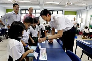 Acting Minister for Education (Schools) Ng Chee Meng (far right) lending a hand to pupils in Xingnan Primary School as they cleaned their classroom yesterday, with Public Hygiene Council chairman Edward D'Silva (in pink shirt) and school principal Ch