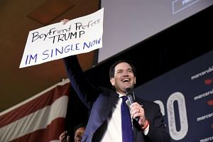 Marco Rubio holds up a supporter's signage on the eve of Super Tuesday in Oklahoma City.