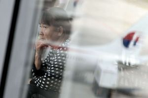 A Malaysian woman looks out at a Malaysia Airlines plane on the tarmac at Kuala Lumpur International Airport.