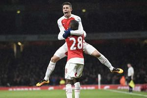 Arsenal's Joel Campbell celebrates with teammate Gabriel (facing) after scoring the opening goal.