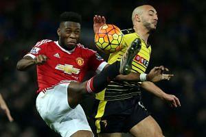 Manchester United's Tim Fosu-Mensah (L) challenged by Watford's Nordin Amrabat.