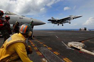 An F/A-18F Super Hornet making an arrested landing on the USS John C. Stennis.