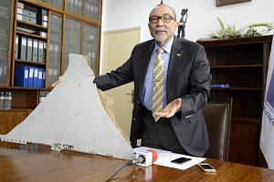 Mozambique Civil Aviation Institute head Joao Abreu with a piece of debris found on a beach that may be from the missing MH370.