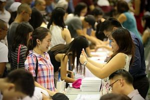 Student Crystal Sia (left), 18, getting the thumbs up yesterday from her Hwa Chong Institution civics tutor Violet Teo for her good results.