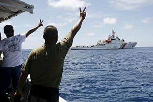 Filipino soldiers gesturing at a Chinese coast guard vessel on the disputed Second Thomas Shoal, part of the Spratly Islands, in 2014. The arbitration case filed by the Philippines on its disputes with China in the South China Sea is drawing a lot of