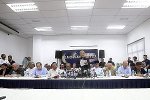 Former Malaysian prime minister Mahathir Mohamad (standing) speaking to the press yesterday after a 58-member group led by him signed what they called a Citizens' Declaration to call for PM Najib's removal from office. The declaration also demanded,