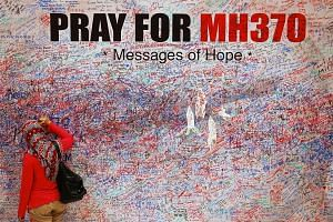 A woman leaves a message of support for the passengers of the missing Malaysia Airlines MH370 in central Kuala Lumpur, on March 16, 2014.