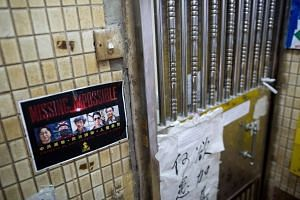 A flyer that reads 'Missing: Impossible' with the photos of five missing booksellers hangs outside Causeway Bay Books store in Hong Kong.