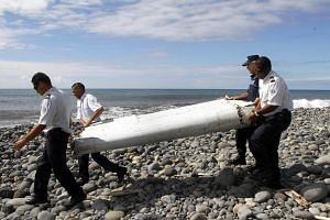 Officers carrying a flaperon from an aircraft apparently washed ashore in Saint-Andre de la Reunion, eastern La Reunion island, France.