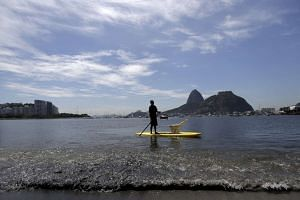 A man paddles his stand-up board at Botafogo Beach, located in Guanabara Bay.