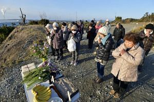 People praying near the sea on the anniversary of the 2011 earthquake and tsunami disaster in Fukushima prefecture, Japan, on March 11, 2016.