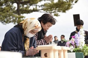 Ms Kiyoi Shida (left), 80, praying by the coast of Obama town in Fukushima prefecture, on the fifth anniversary of the March 11 earthquake in Japan.