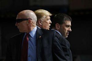 US Secret Service agents surround Donald Trump after the incident.