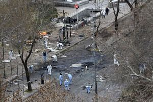 Forensic experts investigate the scene of an explosion on March 14, 2016, a day after a suicide car bomb killed at least 37 people in Ankara, Turkey.