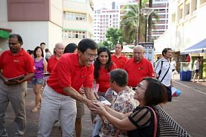 Dr Chee greeting a resident during the SDP's walkabout in Bukit Batok yesterday. He said the party hopes other opposition parties will not contest the seat as it is