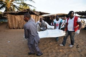 People carry the body of a victim following after gunmen went on a shooting rampage in the Ivory Coast resort of Grand-Bassam, on Sunday.