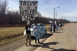 Charles Hambley (left) and Dr Sejal Danawala protest at the Trump rally in Cleveland on Saturday.
