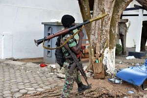 An heavily-armed Ivorian soldier stands guard outside hotel Etoile du Sud in Grand Bassam on Monday, a day after gunmen attacked the Ivory Coast resort town killing 18.
