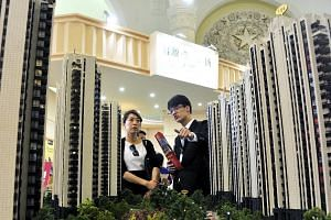 A sales agent (right) and a potential client at a real estate exhibition in Shanghai last April. The diverging property price trend between the top- and lower-tier cities poses a problem for China's housing market policies.
